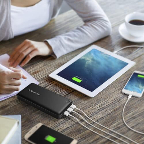 An image showing the best portable charger connected to multiple devices on a desk