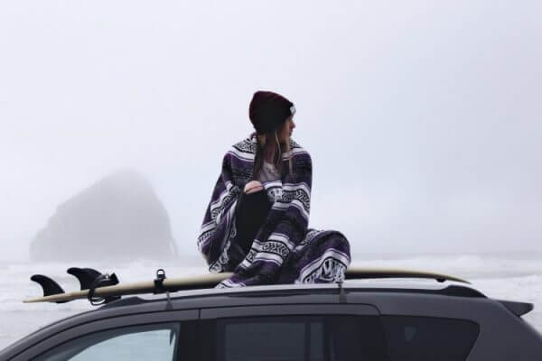 A picture of a girl using one of the best travel blankets to keep herself warm