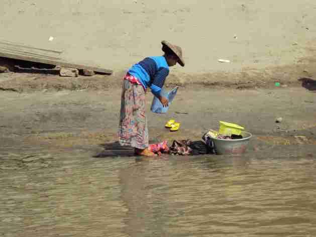 Waschende Frau am Ufer