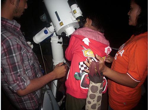 Pengunjung sedang mengintip Jupiter melalui teleskop. Kredit : Aldino