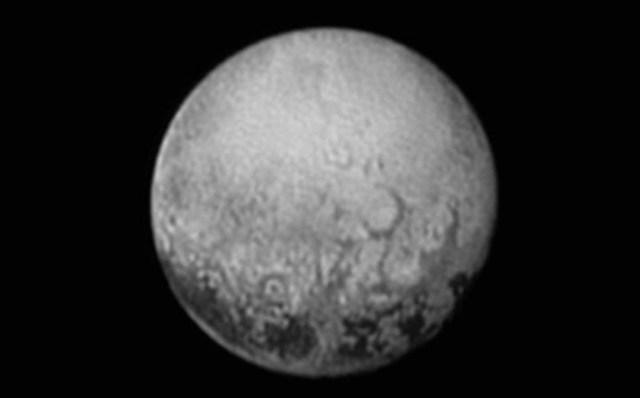 Foto Pluto yang menampakkan 4 bintik gelap di sisi yang saat ini dilihat New Horizons. Kredit: JHUAPL / SwRI