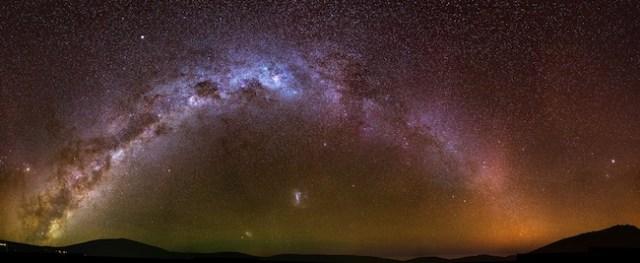 Lengkungan Galaksi Bimasakti yang membentang di langit malam. Terlihat dua galaksi katai di bawahnya; yang lebih terang adalah Awan Magellan Besar sedangkan yang lebih redup adalah Awan Magellan Kecil. Kredit: D. Erkal (Cambridge, UK)