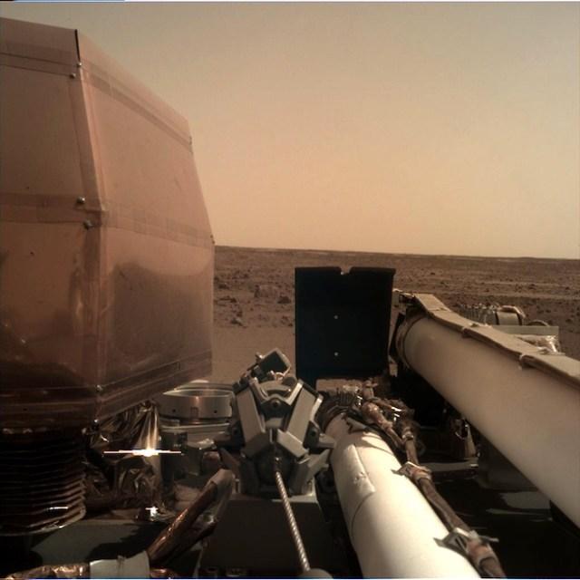 Citra yang diambil InSight setelah panel surya dibuka dan lengan robotik dibentangkan. Kredit: NASA/JPL-Caltech