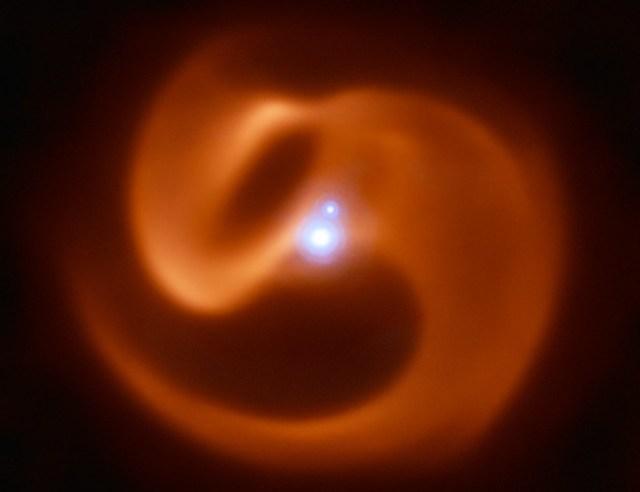 Sistem Apep yang terdiri dari sepasang bintang ganda Wolf-Rayet (titik biru bawah), bintang tunggal (titik biru atas), dan struktur debu berbentuk kincir. Kredit: ESO/Callingham et al.