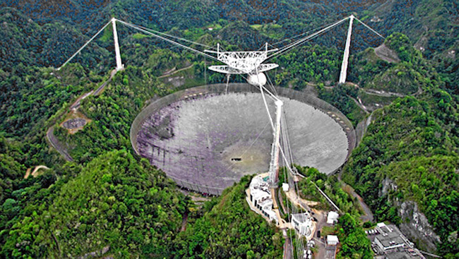 Gambar 3. Observatorium Arecibo, merupakan teleskop radio yang terletak pada kota Arecibo, Puerto Rico. Kredit: Wikipedia