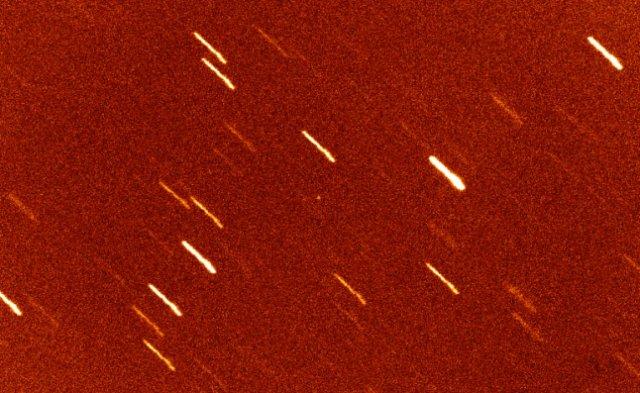 Gambar 3. Asteroid Oumuamua (bintik putih di tengah foto), berdasarkan pengamatan menggunakan teleskop landas bumi William Herschell di Observatorium La Palma, Canary (Spanyol). Garis-garis putih diagonal adalah bintang-bintang di latar belakang, yang mengemuka karena teleskop 'dikunci' ke posisi asteroid. Inilah benda langit pertama yang dipastikan berasal dari luar tata surya. Sumber: Observatorium La Palma, 2017.