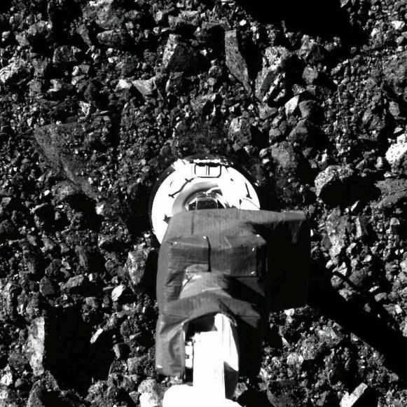 Saat OSIRIS-REx mengambil sampel di Bennu dan tampak debu-debu yang bertebaran. Kredit: NASA