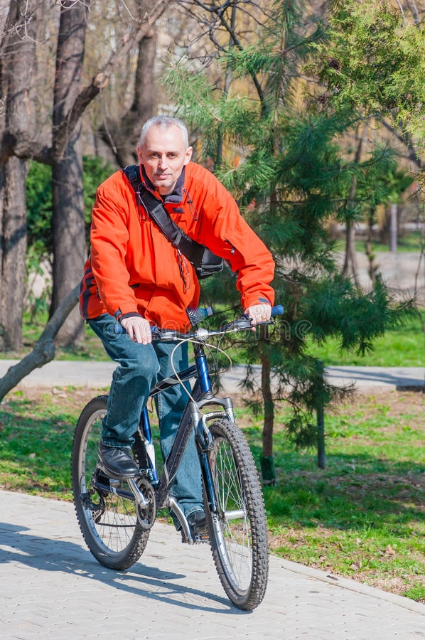 active man riding bike in park stock image image of