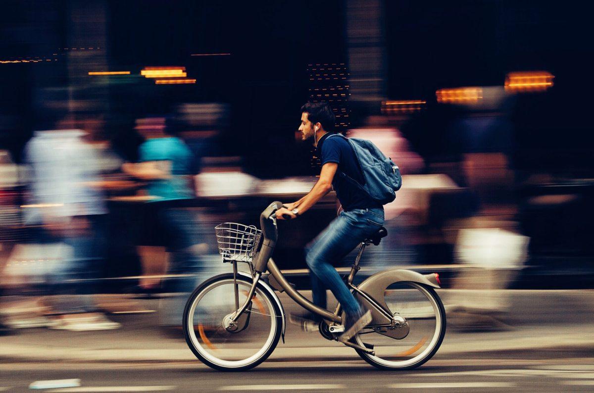 man riding bicycle on city street free stock photo
