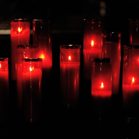 Darkened image of lit candles in red glasses