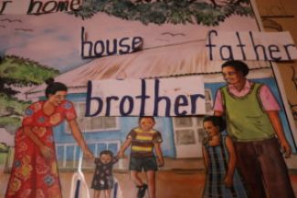 teaching material of a family with a mother, father and two children, the words for different family members, like brother and father, are glued on.