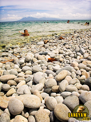 A girl bathes at the shallow waters at Mabua Pebble Beach, Surigao City. Smooth, round and flat stones provides a welcome surprise.