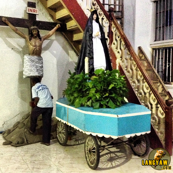 A carroza being readied for the Good Friday procession while a devotee pays his respects to the crucified Christ