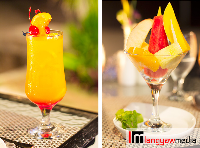 Signature sunset cocktail, left and cut fresh fruit in season with light syrup, right