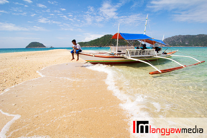 Motorized outrigger boat (banca) docked at the sand.