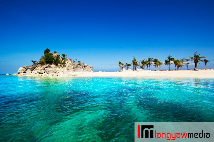 Pristine, turquoise waters, white sandy beach and a rocky outcrop