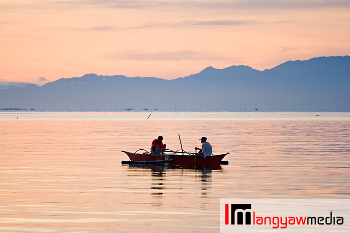 Beautiful morning hue paint the sky before sunrise as two fishermen on their banca in Ormoc City