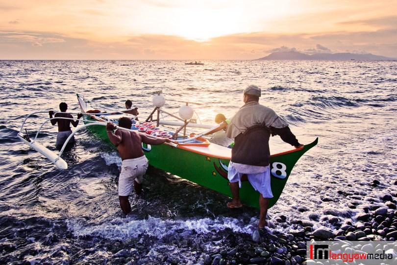 Fishermen doing a 'bayanihan' by helping a fellow fisherman carry his banca to the sea