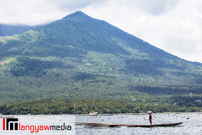 A man stands on his motorized banca as it cruises the placid lake. In the background is the crater of Mt. Asog.