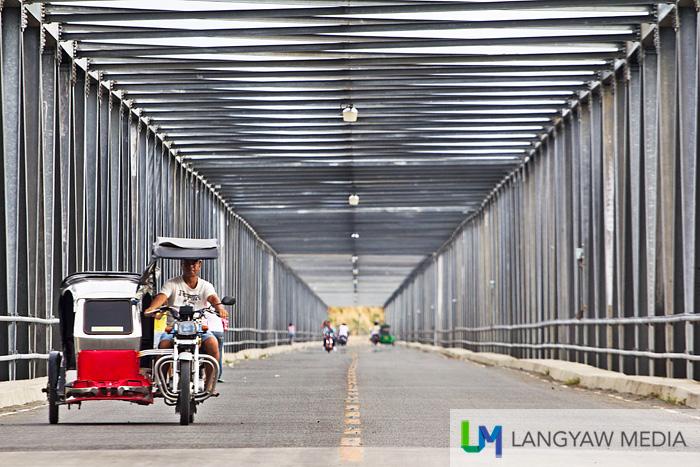 A tricycle passes through the 900 meter Calaba Bridge