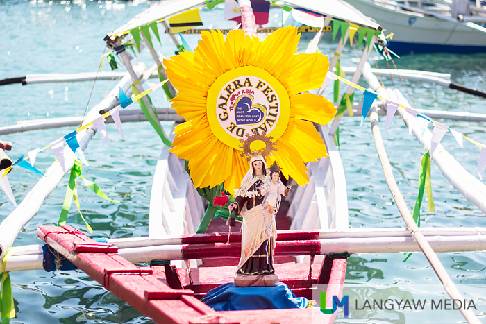 Another outrigger boat with a marian image and floral decor