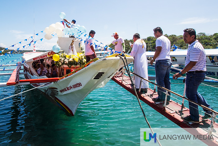 A priest blesses the image and the main boat in the Marian fluvial procession