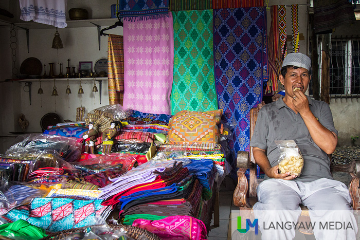 A vendor at the Yakan Weaving Center showing his different textiles and handicrafts from the different muslim tribes of Mindanao