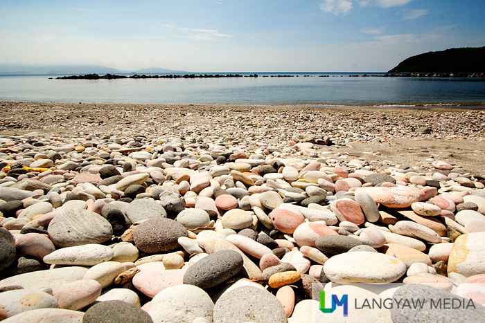 Thousands of smooth round stones scattered along the shore of Resort Beach