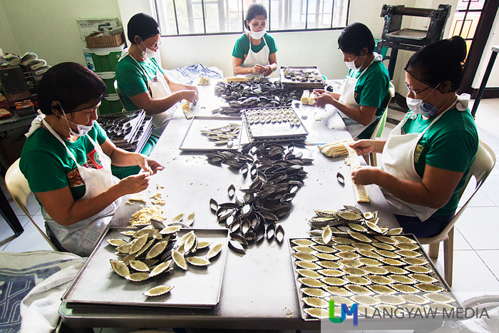 Workers prepare pili tarts