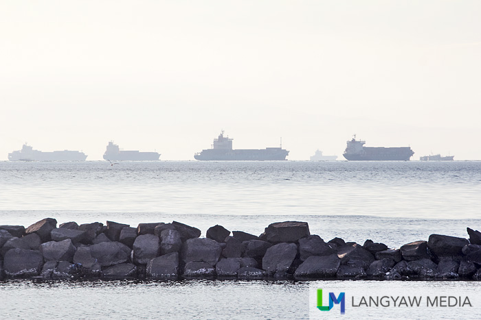 Breakwater with cargo ships in the distance