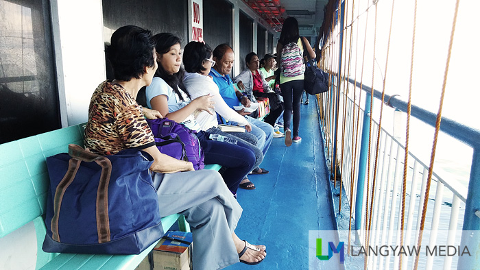 People along the side of the boat