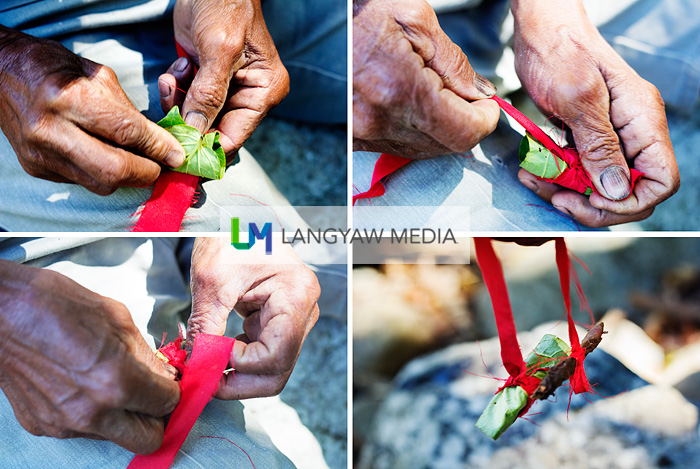Tying a slice of betel nut and leaf with a strip of red cloth