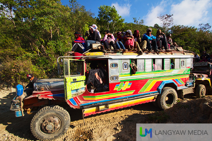 A jeepney filled with people traveling from Tineg to Bangued.