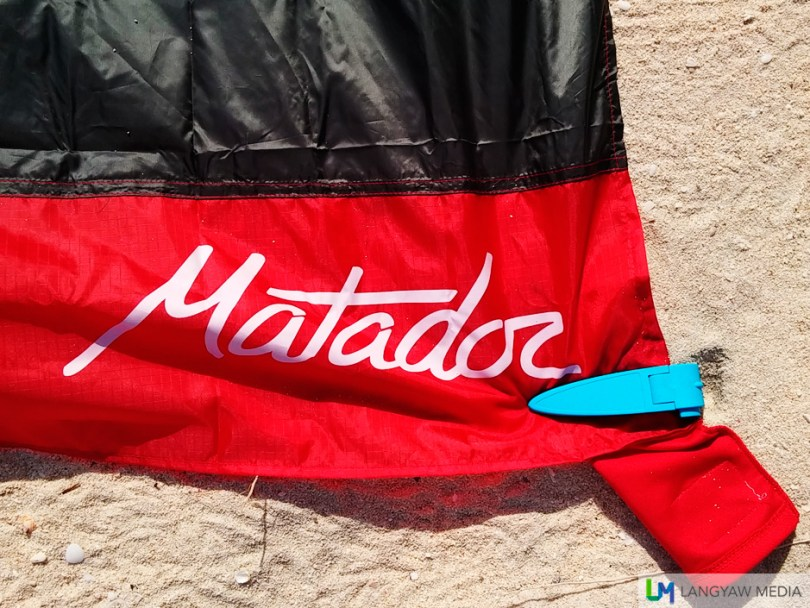 The Matador pocket towel held down by a beach blanket clip