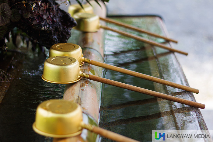 Steel ladles with wooden handles at the chozuya where the Buddhist water purification rite temizu  is performed. It;s located just a few meters from the main entrance of the temple.