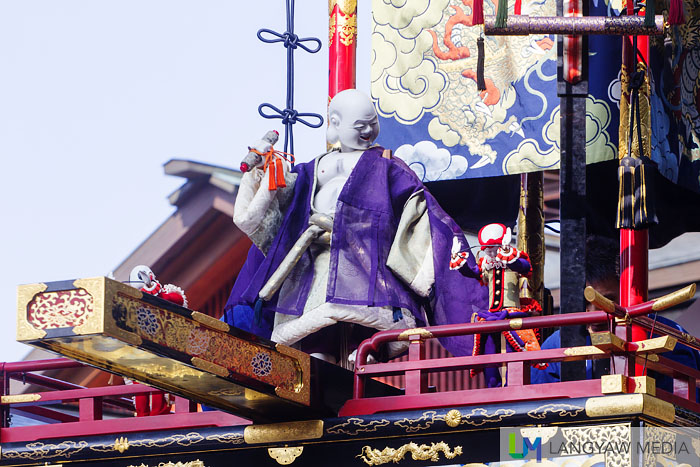 The Priest Hotei as a puppet with two other puppets atop the Hoteitai yatai at the square below the shrine. Skilled puppeters operate these three during the twice a day performance on October 9 and 10.