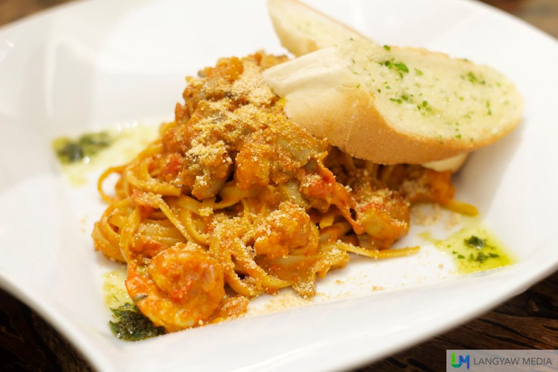 Linguine Aligue: linguine pasta in white wine and crabfat sauce topped with grilled shrimp and musrhoom, garnished with shaved queso de bola (emmental cheese) and toasted french bread slices. Another recommended dish, it's rich yet delicious.