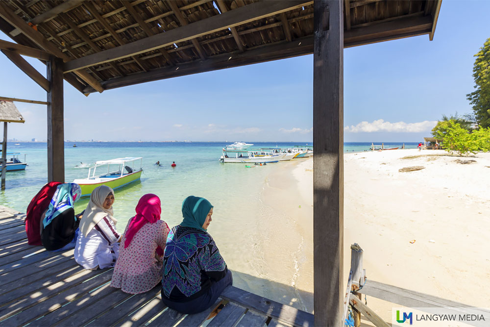 Muslim women at the wooden jetty of Pulau Samalona enjoying the view