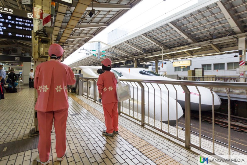 Cleaning crew in sakura pink uniform waiting for the train to stop