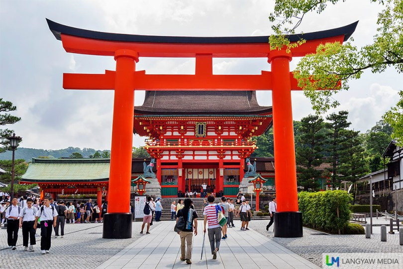 The torii gate at the entrance of the Fushimi Inari Shrine. The rōmon gate, the one after the torii, is the main entrance to the shrine and was built in the 16th century