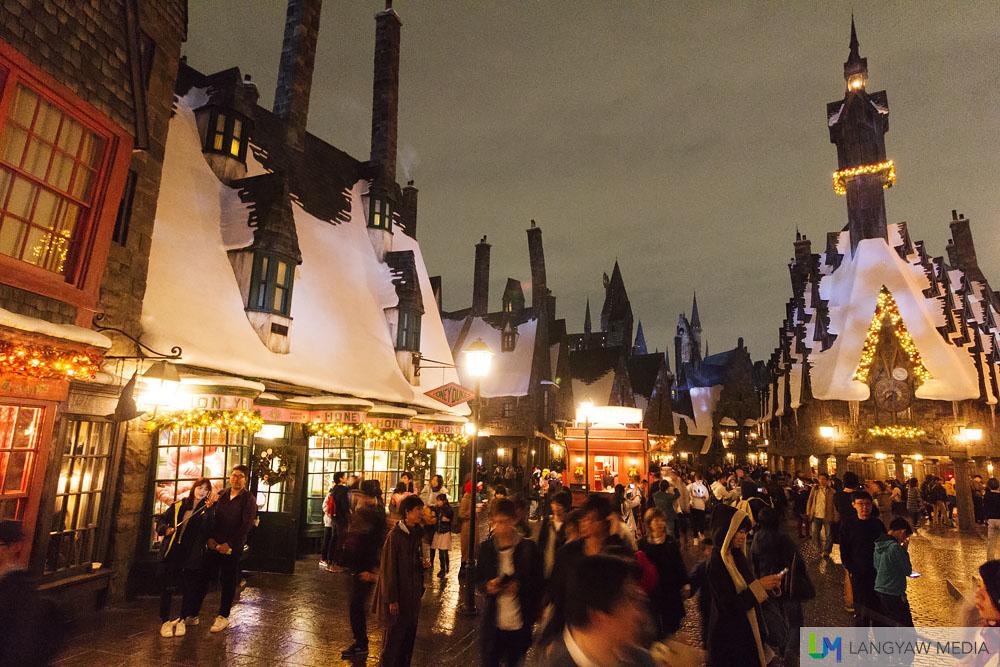 Hogsmeade Village is aglow with warm lights and festive decors