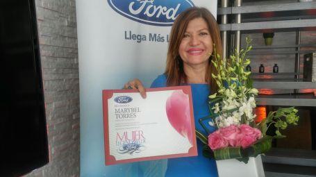 Marybel Torres muestra feliz y orgullosa su diploma de reconocimiento.