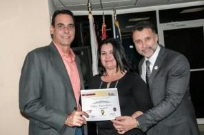 La escritora Odalys Interian Guerra, ganadora del cuarto lugar, recibe el reconocimiento de parte de Albert Collazo, gerente de comunicaciones de Ford y Luis Castillo, gerente de comercialización de PAWA.