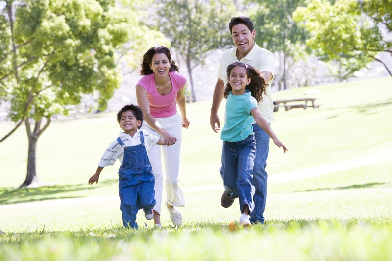 familia latina corriendo por un parque.