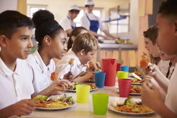 Niños sentados en una mesa dentro de una cafetería escolar.