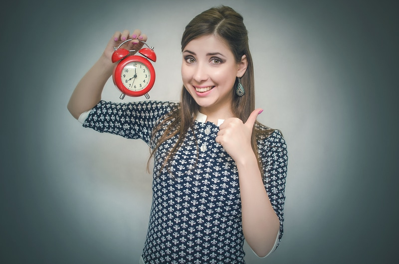 joven con una sonrisa apuntando con un dedo a un reloj.