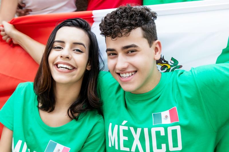 Dos jóvenes sonriendo y alzando una bandera mexicana.