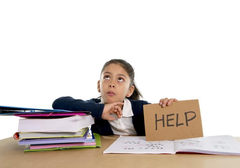 """una niña rodeada de libros de lectura sosteniendo una pancarta que dice, """"ayuda"""""""