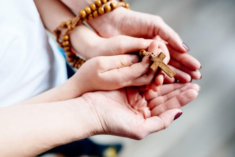 Un niño sujetando un rosario en sus pequeñas manos