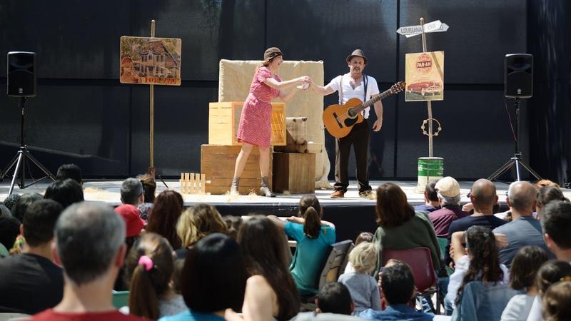 Panorama de una audiencia viendo un cantante con guitarra en un escenario